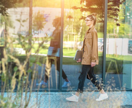 Young girl in glasses going to work. Woman in the city.