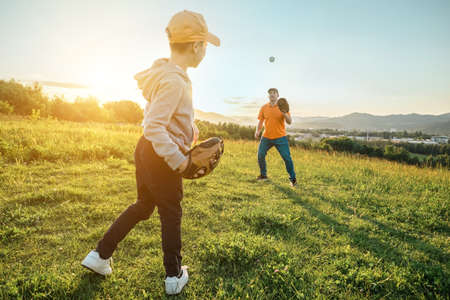 Father and son playing in baseball. Playful Man teaching Boy baseballs exercise outdoors in sunny day at public park. Family sports weekend. Father's day. Stockfoto