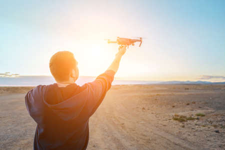 Man controlling fly drone on the seashore at sunset in summer day. Freedom, Family, Travel, Journey, Togetherness.
