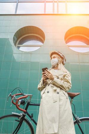 Woman in protective maskin, in helmet using her smartphone device. Female go to work on his sport retro bike. Girl standing on green background. 版權商用圖片