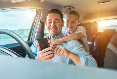 Happy father and son sitting in car and using smartphone in summer sunny day. Happy family travels 版權商用圖片