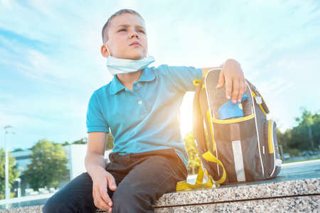 Boy, schoolboy in protective mask sits near the school in sunny September day 版權商用圖片