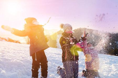 Children playing snowballs, having fun in the snow, happy winter holidays. 版權商用圖片
