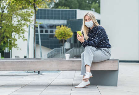 Female wearing masks working over smartphone, while sitting on seat in town. Woman face wearing masks. Long distance communication. Staying connected, 4K slow motion video.