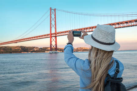 Young traveler woman with smartphone takes pictures in Lisbon of city near the bridge under sunlight in sunny summer day. 版權商用圖片