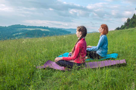 Mother and daughter doing yoga in nature, fresh air in the park