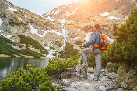 Man hiker, hiking backpacker traveler camper walking on the top of mountain in sunny day under sun light. Beautiful mountain landscape view. 版權商用圖片