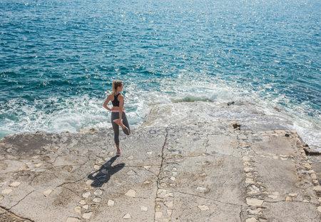 Woman running training on the coastline under sunlight in sunny summer day