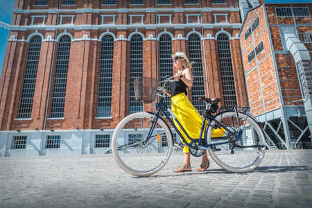 Happy traveler woman with her bicycle rides in city and looking on streets view in sunny summer day. Freedom, Travel, Journey, concept.