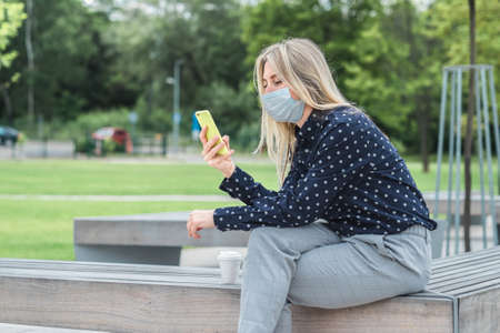 Female wearing masks working over smartphone, while sitting on seat in town. Woman face wearing masks. 版權商用圖片