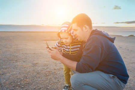 Father and son controlling fly drone on the seashore at sunset in summer day. Freedom, Family, Travel, Journey, Togetherness.