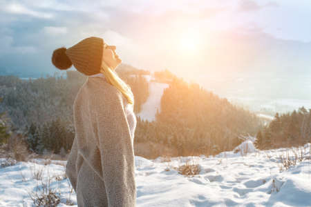 Happy woman traveler on the top of mountain and looking on beautiful winter snowy view. 版權商用圖片