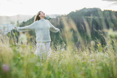 Portrait happy woman enjoying sunset stay on the green grass on the forest peak of mountain. Fresh air, Travel, Summer, Fall, Holidays, Journey, Trip, Lifestyle. 版權商用圖片