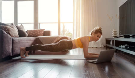 Woman doing online yoga at home. Female trener teaches asana in video conference. Health care, authenticity, sense of balance and calmness. 版權商用圖片