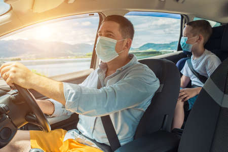 Father and son in protective masks driving car, Happy traveler family. Bonding Travel, Summer, Holidays, Journey, Trip concept.