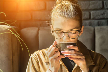 Young woman drinking coffee cup and sitting in cafe. Girl in glasses pauses after work. 版權商用圖片