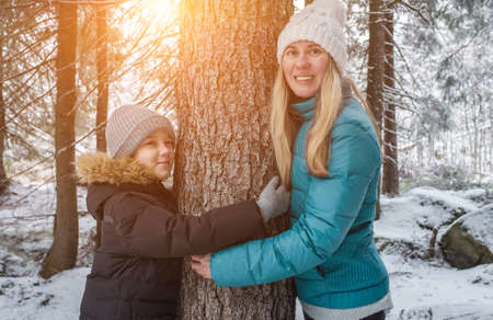 Mother and son in forest on winter day. Hiker hugging tree trunk. Save of nature and the planet.