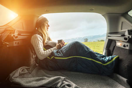 Girl resting in her car. Woman hiker, hiking backpacker traveler camper in sleeping bag, drinking hot tea and relaxing on top of mountain. Health care, authenticity, sense of balance and calmness. 版權商用圖片