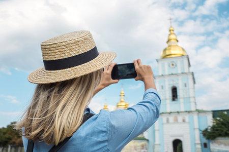Woman traveler tourist using smartphone, taking photo of church Kiev, Ukraine in summer sunny day.