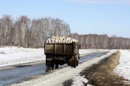 Old truck takes firewood to the village along a muddy winter road