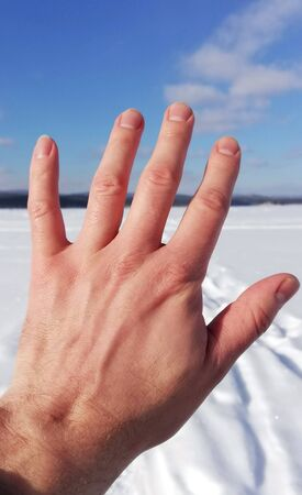The hand of a man closes the blue sky and winter nature Stockfoto