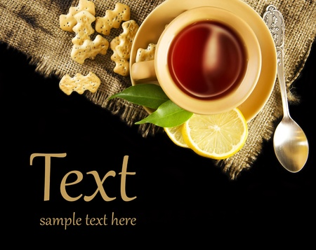 A cup of tea with lemon and crackers photo