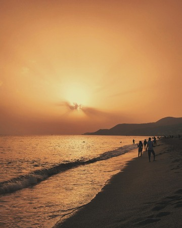 Sea sunset with mountains. Seascape on beach.