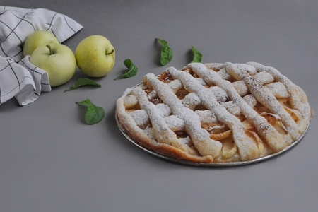 Apple pie with white towel on gray background. Dessert. Homemade cake with apples. Autumn flatlay. Homemade pie with mint and sugar powder.