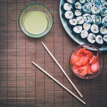 Homemade sushi with wasabi sauce, ginger and sushi sticks on wooden rug