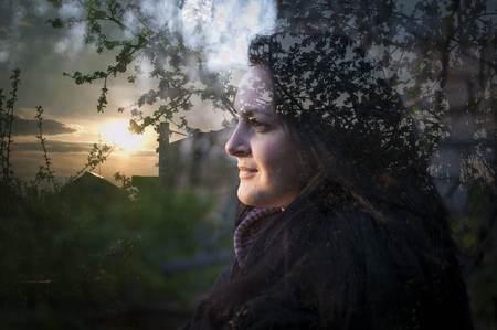 Multi exposure of girl and nature. Girl looking at the sun 版權商用圖片