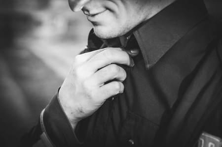 L'homme corrige sa chemise à col. photo en noir et blanc Banque d'images