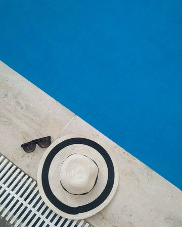 Straw hat with sunglasses near the pool classic blue color of the year 2020.