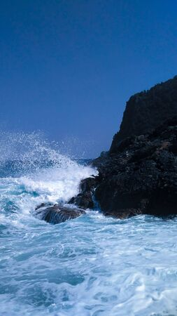 Wave hits the rock. Big waves in the sea. Island without people