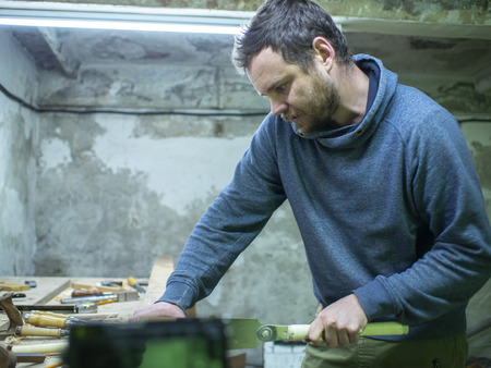 woodworker with a beard sawing a wooden beam with a hand saw. a carpenter sawing a piece of wood