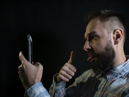 fashionable man with a beard and mustache grimaces and takes a selfie on the phone on a black background Standard-Bild - 120003225