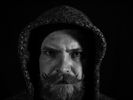 portrait of a man with a beard and mustache in the hood with a serious face on a black background.black and white photo