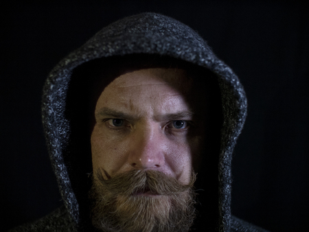 portrait of a man with a beard and mustache in the hood with a serious face on a black background Imagens