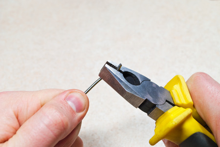 Working with Pliers. A man working