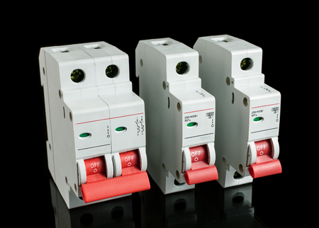 electrical equipment: Various automatic circuit breakers, isolated on black background. Electric fuse.