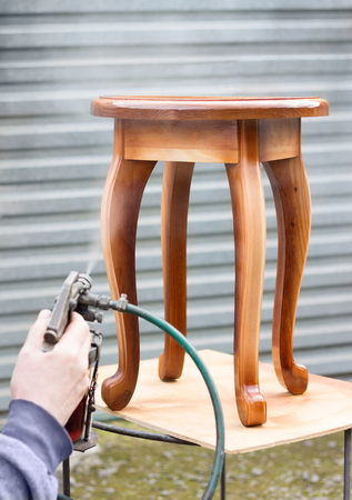 pulverizer: Carpenter is covering stool by lacquer. Furniture varnishing using sprayer (pulverizer).