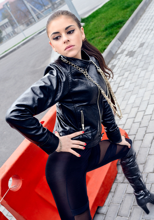 Sexy brunette girl with black eyes. Young female model portrait wear leather jacket black leggings and leather boots. Attractive Fashion lady with long brown hair wear cool outfit and high heels Stock Photo