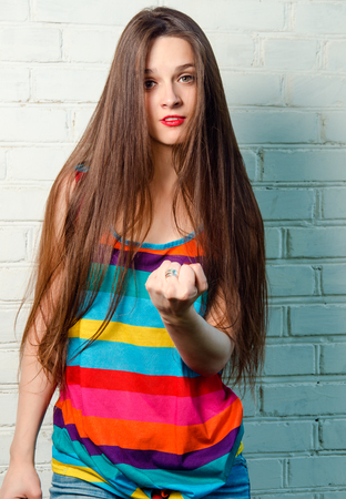 threatens: Girl funny threatens with fist. Young female model portrait wearing colorful shirt. Fashion lady with long brown hair wear cool outfit Stock Photo