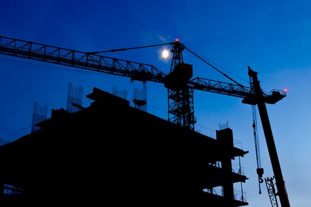 unfinished building: Construction Site. Industrial construction cranes and building silhouettes on night sky. Beautiful colorful night landscape.