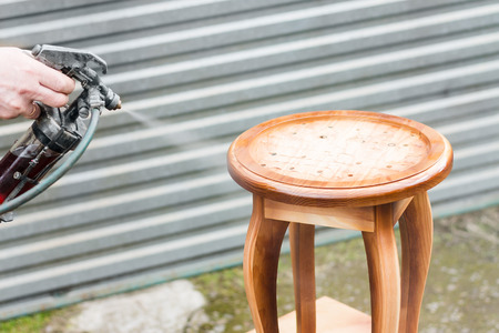 pulverizer: Carpenter is covering stool by lacquer. Furniture varnishing using sprayer or pulverizer
