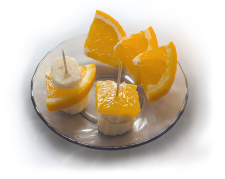 Banana and orange on a saucer