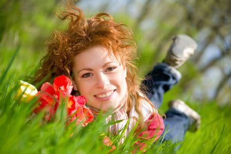 Beautiful young red-haired woman with red tulips on green meadow photo