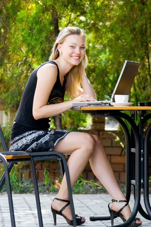 Happy beautiful model sitting in cafe with laptop photo
