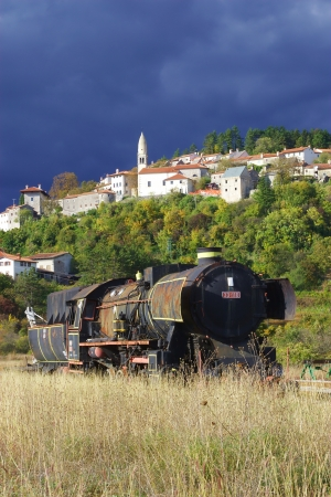 daniele: Old abandoned locomotive before Stanjel - San Daniele del Carso, Slovenia, with stormy sky in background Stock Photo