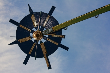 A weather vane with wind rose before blue sky and light clouds photo