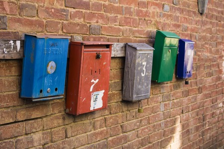 five mailboxes on a brick wall
